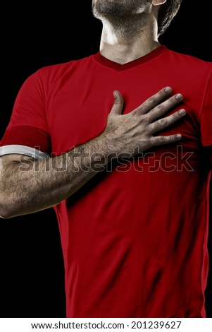 Swiss soccer player, listening to the national anthem with his hand on his chest. On a black background.