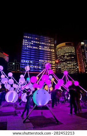 SYDNEY,AUSTRALIA - MAY 26,2015: People enjoying a light sculpture at the Vivid festival. Taking place annually in Sydney, Vivid is the world's largest open-air art gallery.