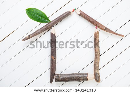 Symbol of a house made up of wooden pencils and green leaf