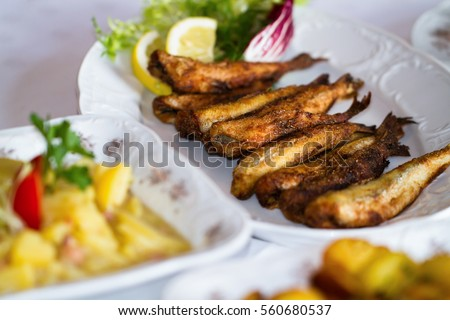 Table arrangement in the restaurant with fried potatoes fried fish fillet and side dishes on the plate