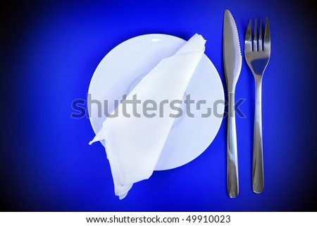 Table serving-knife, fork  and silk napkin on blue   background.Spotlight source on top and in center.