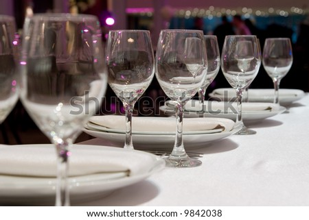 Table setting in restaurant with row of wineglasses, plates and Napkins