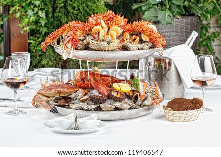 table with a bottle of wine, seafood and wine glasses