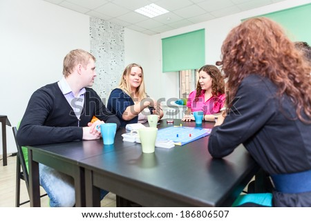 Table with board game and funny young adults playing