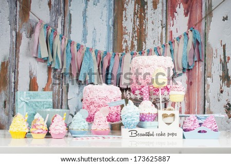 Table with loads of cupcakes and cakepops and birthday cakes