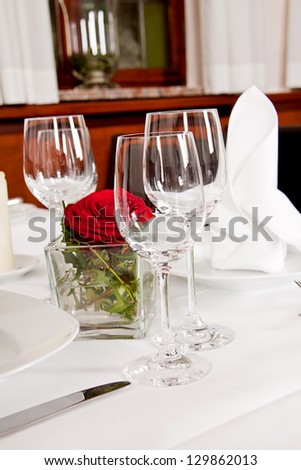 tables in restaurant with white tablecloth and elegant dish and silverwear