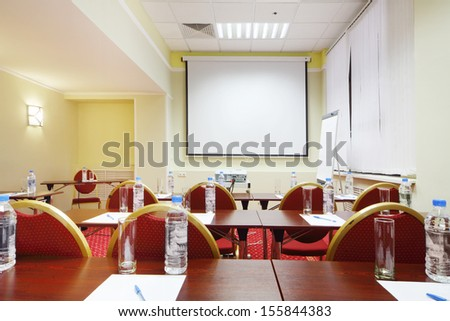 Tables with bottles and glasses, back of red chairs and projector in room for business trainings.