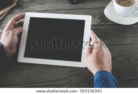 Tablet computer with blank screen for your text message in men hands close up