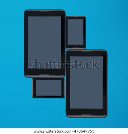 Tablet pc and smartphone lying side by side isolated on blue background with soft shadow