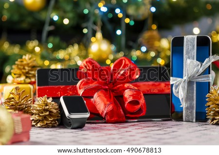 Tablet pc, smartphone and smartwatch with gifts and decorations in front of Christmas tree. Focus on smartphone.
