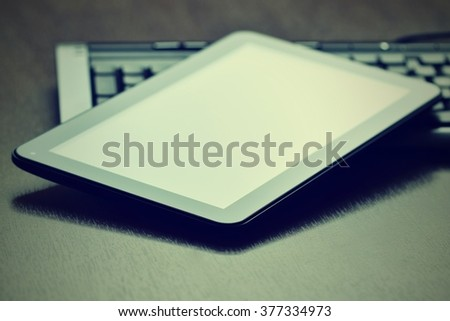 Tablet positioned on the keyboard of a personal computer. Technological background,  laptop with digital tablet isolated on wooden desk.