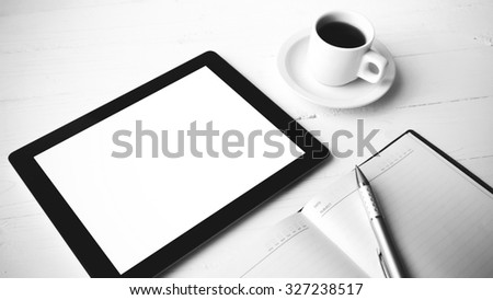 tablet with office supplies over white table black and white color style