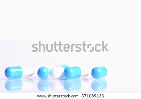 Tablets isolated on a white background. Reflection of pills on a glass. Medicine´s background. Pharmacy. Close up of capsules.