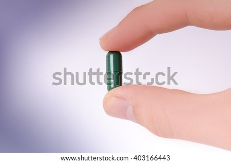 Tablets on a white, blue background. Hand keep a pill. Medicine´s background. Pharmacy. Close up of capsules.