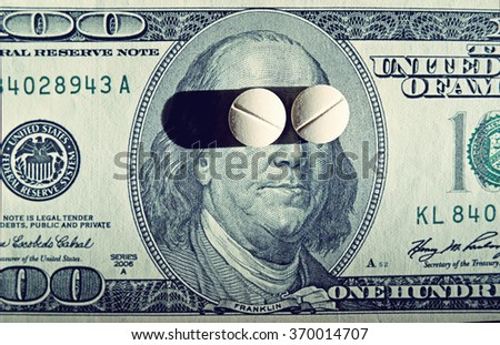 Tablets on dollar bills (treatment, addiction, aging - concept). Vintage effect.