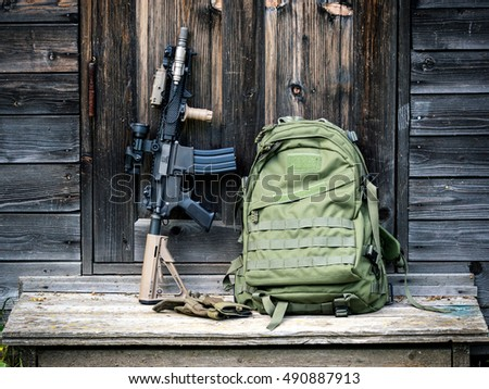 Tactical carbine and green backpack on the steps of the old house