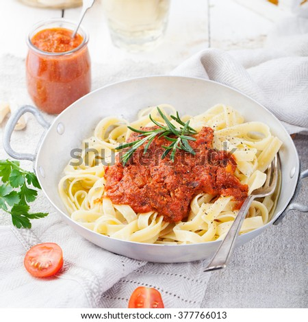 Tagliatelle pasta with tomato sauce and red pesto Italian cuisine
