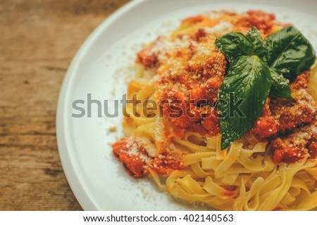 tagliatelle with bolognese sauces served with parmesan cheese and a fresh basil