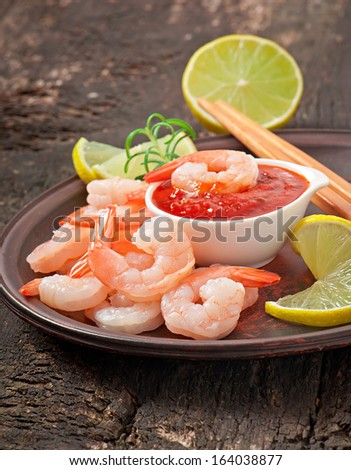 tails of shrimps with fresh lemon and rosemary in plate on wooden old background