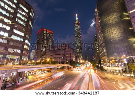 TAIPEI, TAIWAN - 23 NOVEMBER, 2015: The moon shines over the Taipei World Trade Center and Taipei 101 in Xinyi Business District at dusk on Nov. 23, 2015 as traffic passes through a busy intersection.