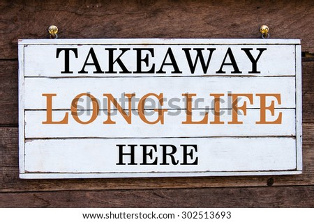 Takeaway Long Life Here Inspirational message written on vintage wooden board. Motivation concept image