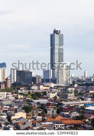 Tall hotel and office building that contrast with low rise residential neighborhood in Jakarta, Indonesia capital city