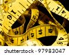 Tangled yellow tape measure with centimeters and inches - stock photo