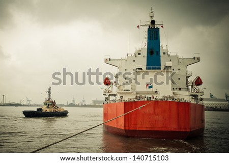 Tanker ship being tugged into a port