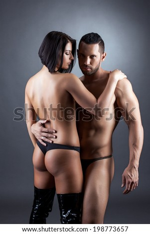 Tanned topless lovers hugging in front of camera