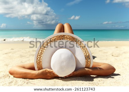 Tanned young girl lying on the beach sand