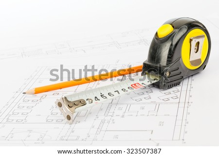 Tape measure with pencil on draft background