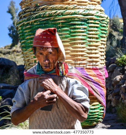 TAQUILE ISLAND, PUNO, PERU. MAY 31, 2013: Unidentified single man in traditional clothes carrying big rattan baskets,  on the Taquile island, in Titicaca lake
