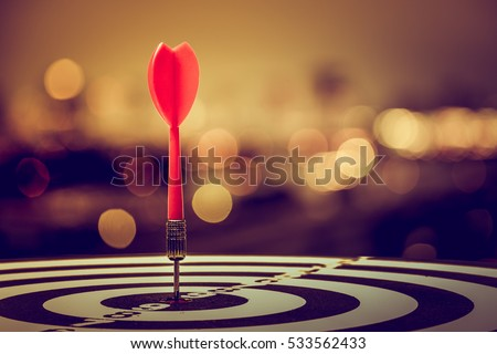 target dart with arrow over blurred bokeh background ,metaphor to target marketing or target arrow concept.