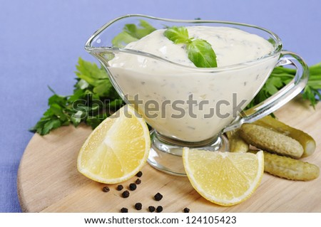 Tartare Sauce  in a  gravy boat with cucumber and lemon on wooden cutting board