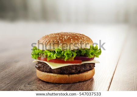 Tasty and appetizing Cheeseburger On Wooden Table