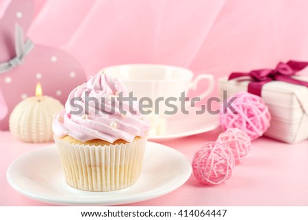 Tasty cupcake with gifts and decorations on pink background
