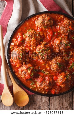 Tasty food: Meatballs albondigas with tomato sauce on a plate on a table close-up. vertical view from above