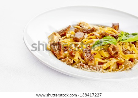 Tasty food. Pasta with roasted meat over white background.