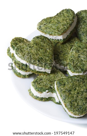 tasty green heart shaped cookies with spinach and cream cheese isolated on white background close-up. vertical