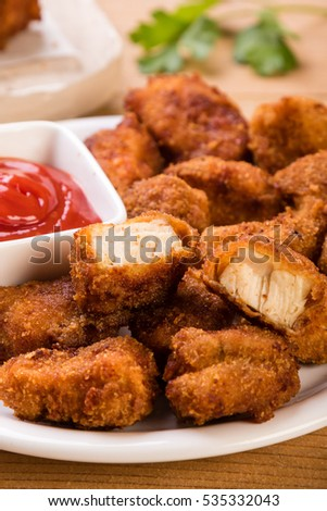 tasty homemade chicken nuggets with ketchup on plate
