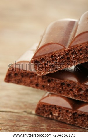 Tasty porous chocolate on wooden table
