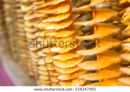 Tasty potato chips on a thin wooden stick.  Blurring background