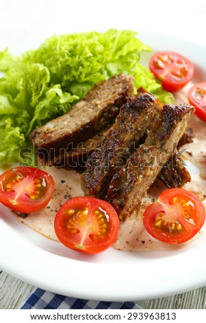 Tasty slices of meat with sauce and cherry tomato on plate close up
