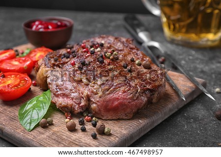 Tasty steak with tomatoes and spices on cutting board