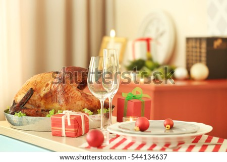 Tasty turkey, plates and glasses prepared for Christmas dinner, on blurred background