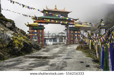 Tawang, Arunachal Pradesh, India. The Buddhist architectural and colorful gateway into Tawang on highway 229 on a misty morning and Himalayas in the background near Tawang, Arunachal Pradesh, India.