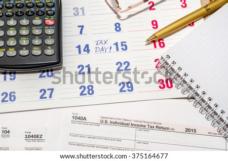 tax form with calculator, pen, notepad above paper calendar
