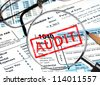 Tax forms under magnifying glass revealing an audit - stock photo