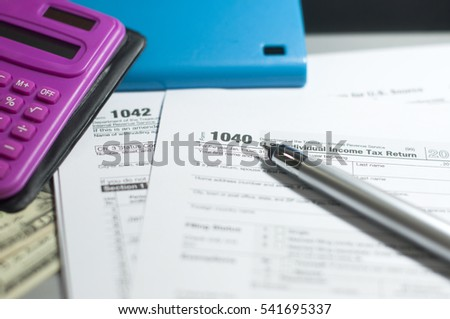 Tax Season: 1040 U.S. Individual Income Tax Return Form horizontal top view with office laptop bank notes background and pink calculator blue smart phone a metallic pen prepare for taxation foreground