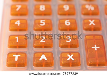 Taxation concept - Orange calculator with the word TAX added across the bottom